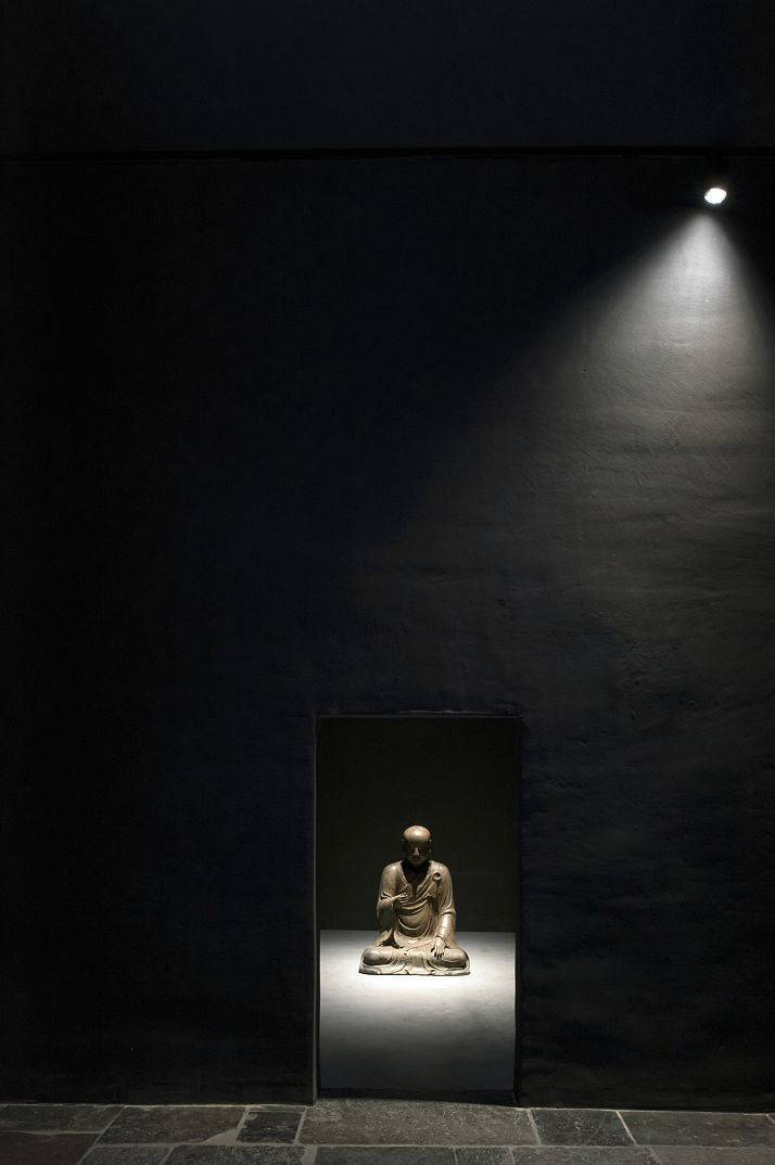 The figure of a meditating Buddhist 'Lohan' priest made of varnished wood in the so-called Black Box is effectively illuminated by a Parscan spotlight. A rotary control on the luminaire allows the spotlight with 15W installed load to also be dimmed for the very soft lighting effect. Another Parscan spotlight accentuates the exterior wall of the Black Box.