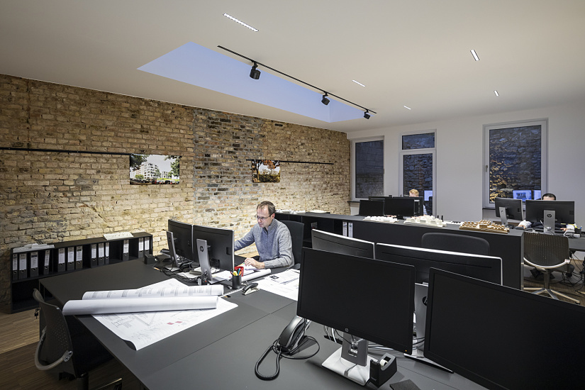 The largest office room is on the ground floor of the existing building. A total of eight workstations illuminated by six ceiling-integrated Compar downlights, each with a connected load of 27W and oval wide flood light distribution, are illuminated without glare. The light beam of each of these luminaires creates a wide oval for illuminating the desk surface and immediate work surroundings in compliance with standards. Parscan track spotlights with oval flood distribution illuminate drawings and plans displayed on the wall.