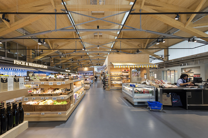 Inside the nearly 1,000-square-metre store, the design is also dominated by wood – untreated wooden trusses for the hall's timber framed roof structure – and glass; combined with the polished concrete flooring, it lends the hall a modern, airy character. ERCO Optec spotlights are mounted on a black track system.