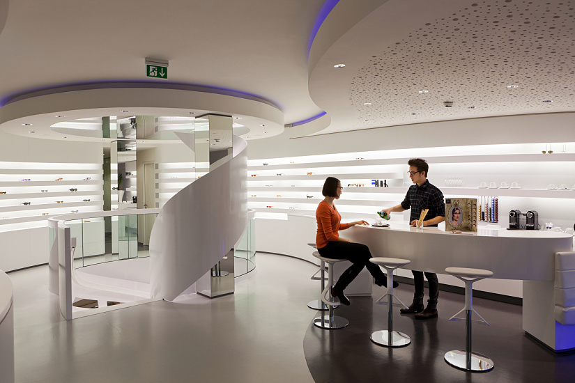 Round recessed luminaires were unobtrusively integrated into the ceiling, allowing the linear geometry of the space to dominate. Zeiss Optik Kästner, Stuttgart. Architect and lighting designer: Labor Weltenbau, Stuttgart. Photographer: Thomas Pflaum.