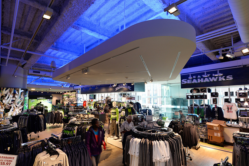 Blue, diffuse ceiling lighting gives the shop an impression of height, and with warm white accent lighting creates a contrast-rich sense of emotion for the products. The Pro Shop in the CenturyLink Field soccer stadium, Seattle / USA. Architect: Rossetti Architects, Detroit / USA. Lighting designer: Devki RajGuru, LittleFish Lighting Inc., Redmond / USA. Photographer: Arnaldo Dal Bosco.