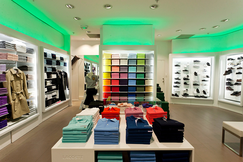 Light coves with changing colours reference the apparel in the shelves, communicating a holistic brand experience. Lacoste Showroom, Aubervilliers. Architect: Devanlay. Photographer: Dirk Vogel.