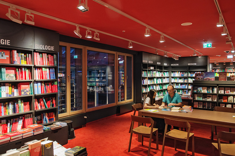 The red ceiling forms a companion piece to the red carpet of the bookstore. White luminaires on white tracks give the space a linear dynamism. Dussmann das KulturKaufhaus GmbH, Berlin. Architect: ROBERTNEUN Architekten, Berlin. Photographer: Rudi Meisel.