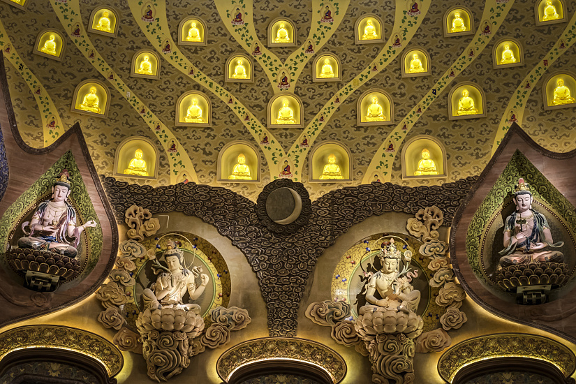 Works of art completely cover the walls and ceiling. Accent lighting draws visitors' attention to the Buddha figures.