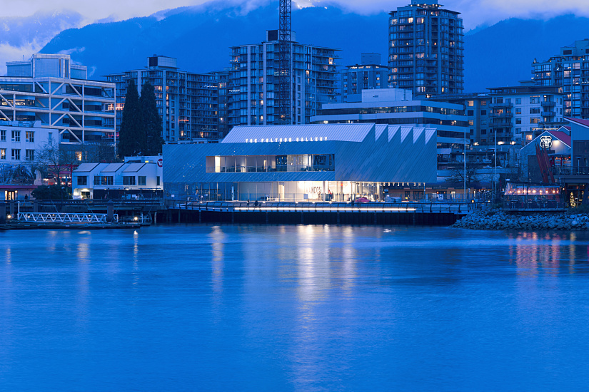 "The striking new gallery building consisting of around 2,000 square meters of floor space is located on an exposed site right on the harbor, with the stunning Vancouver skyline as a backdrop. The upper floor, enclosed on three sides, comprises the actual exhibition spaces. Only the so-called ""exterior deck"" with its band of windows offers a panoramic view across the harbor."