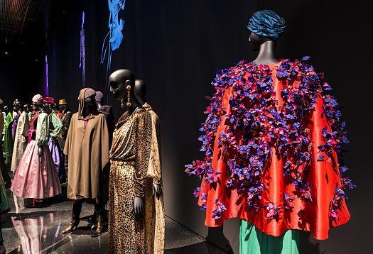 Les œuvres maîtresses du génie créatif Yves Saint Laurent bénéficient d'une mise en lumière spectaculaire et d'une mise en scène opulente dans la salle d'exposition entièrement noire.